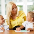 Teacher helps to little girls to make an exercises in classroom — Stock Photo #6302511