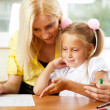 Young pretty teacher helping her little students in classroom — Stock Photo #6302517