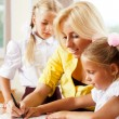 Young pretty teacher helping her little students in classroom — Stock Photo #6302520