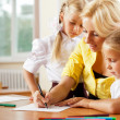 Young pretty teacher helping her little students in classroom — Stock Photo #6302522