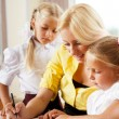 Young pretty teacher helping her little students in classroom — Stock Photo