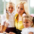 Young pretty teacher helping her little students in classroom — Stock Photo #6302525