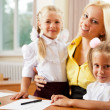 Young pretty teacher helping her little students in classroom — Stock Photo #6302528