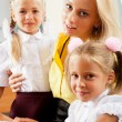 Royalty-Free Stock Photo: Young pretty teacher helping her little students in classroom