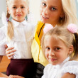 Young pretty teacher helping her little students in classroom — Stock Photo #6302529