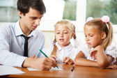 Teacher helping elementary school pupils with their tasks — Stock Photo