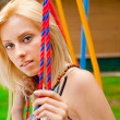 Portrait of pretty young woman swinging on playground at park an — Stock Photo #6334639