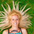 Young woman laying on green grass with hair like a sun around he — Stock Photo #6334648