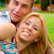 Portrait of beautiful young couple sitting on ground in park rel — Stock Photo #6334690