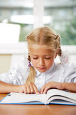 Ritratto di una giovane ragazza della scuola presso il desk. — Foto Stock
