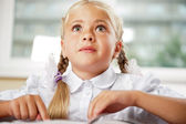 Portrait of a young girl in school at the desk. — Stock Photo