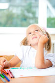 Little girl looking for a drawing concept wile painting picture — Stock Photo