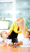 Young pretty teacher helping to her students to make exercise in — Stock Photo