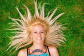 Jeune femme portant sur l'herbe verte avec des cheveux comme un soleil autour il — Photo