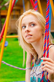 Portrait of pretty young woman swinging on playground at park an — Stock Photo