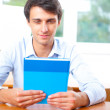 Portrait of a young handsome man with a book indoors — Stockfoto #6418888