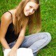 Beautiful female student outdoors with a book at campus park — Stock Photo