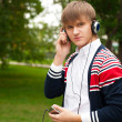 Student listening language course in headphones outside school — ストック写真
