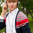 Student listening language course in headphones outside school — Stock Photo