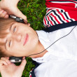 Student outside laying on grass and listening music school. Phot — Stock Photo #6419041