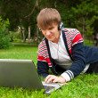 Student laying on grass and using laptop outside school — Stock Photo