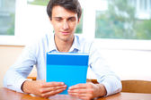 Portrait of a young handsome man with a book indoors — Stock Photo