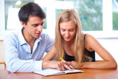 Portrait of teacher helping young student with her studies in co — Stock Photo