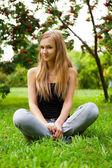 Mooie vrouwelijke student buiten zitten op gras op campus par — Stockfoto