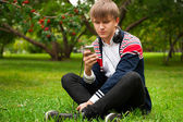Student outside sitting on green grass and listening music via h — Stock Photo