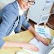 Stock Photo: Beautiful business woman smiling while working with reports and