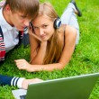 Happy young couple using laptop while lying on grass — Stock Photo #6472332