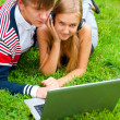 Happy young couple using laptop while lying on grass — Stock Photo