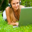 Stock Photo: A smiling young girl with laptop outdoors listening music by hea