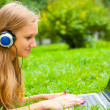 A smiling young girl with laptop outdoors listening music by hea — Stock Photo
