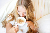 Smiling woman drinking a coffee lying on a bed at home or hotel. — Stock Photo