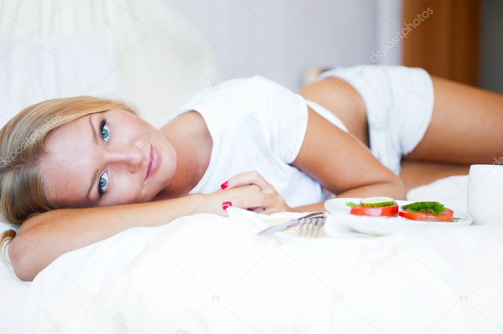 Woman having breakfast in bed. Healthy continental breakfast. Caucasian woman smiling looking at camera. — Stock Photo #6472274