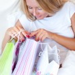 Royalty-Free Stock Photo: Young happy attractive girl unpack shopping bags in bedroom or h