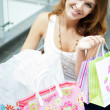 Photo of young joyful woman with shopping bags on the background — Stockfoto