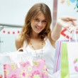 Photo of young joyful woman with shopping bags on the background — 图库照片
