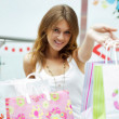 Photo of young joyful woman with shopping bags on the background — ストック写真