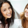 Two women whispering and smiling while shopping inside mall — Stock Photo #6487107