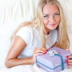 Bedroom surprise present - young happy woman in bedroom — Stock Photo