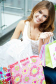Photo of young joyful woman with shopping bags on the background — Стоковое фото