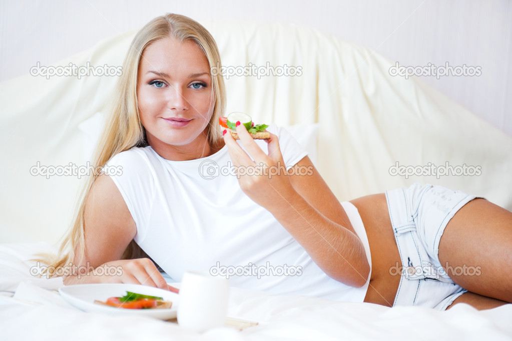 Woman having breakfast in bed. Healthy continental breakfast. Caucasian woman smiling looking at camera. — Stock Photo #6487044