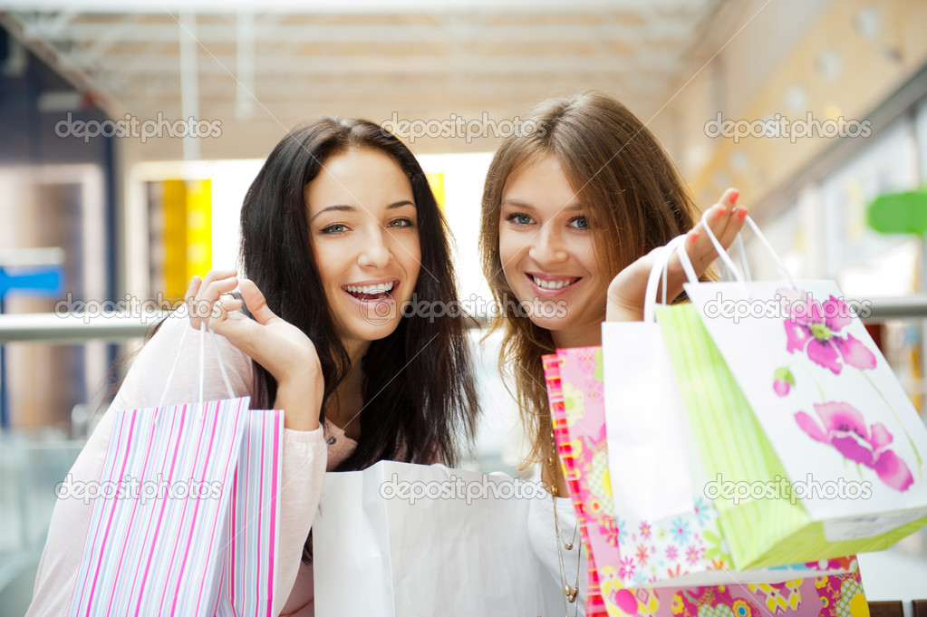 Two excited shopping woman together inside shopping mall laughing and gossip. Horizontal Shot — Stock Photo #6487095