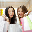 Стоковое фото: Two excited shopping woman together inside shopping mall. Horizo