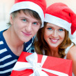 Portrait of young pretty couple standing indoors wearing Santa C — Stock fotografie #6567842