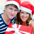 Portrait of young pretty couple standing indoors wearing Santa C — Stock Photo #6567842