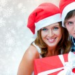 Portrait of young pretty couple standing indoors wearing Santa C - Stock Photo