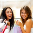 图库照片: Two excited shopping woman together inside shopping mall. Horizo